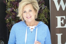 Fashion Blogger 50 Is Not Old wearing a bright blue lace-up hoodie