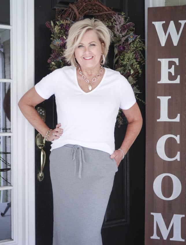 Fashion Blogger 50 Is Not Old is wearing a white v-neck t-shirt with a medium gray jogger pencil skirt, and silver jewelry