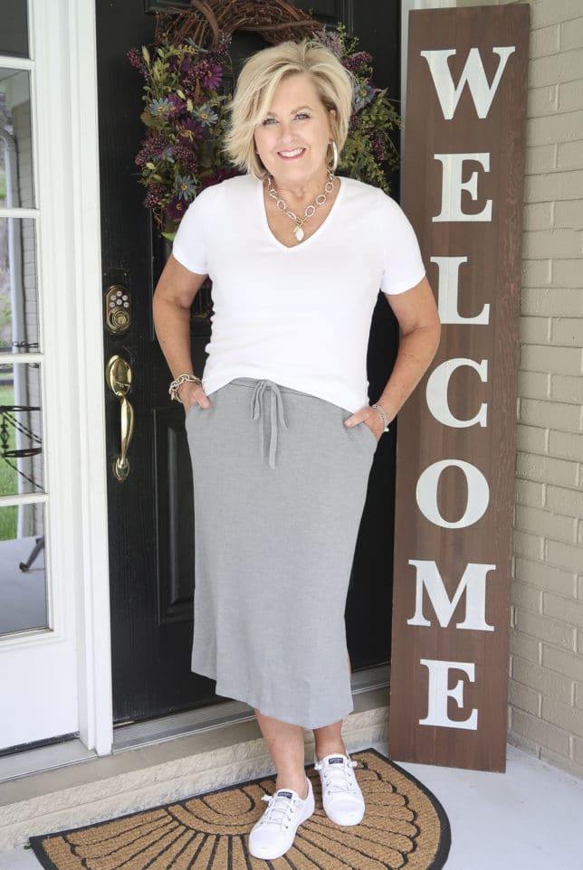 Fashion Blogger 50 Is Not Old is wearing a white v-neck t-shirt with a gray jogger pencil skirt, sneakers, and silver jewelry