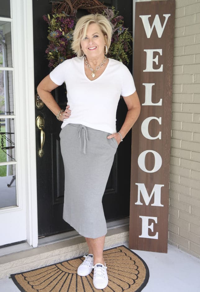 Fashion Blogger 50 Is Not Old is wearing a white v-neck t-shirt with a medium gray jogger skirt, sneakers, and silver jewelry