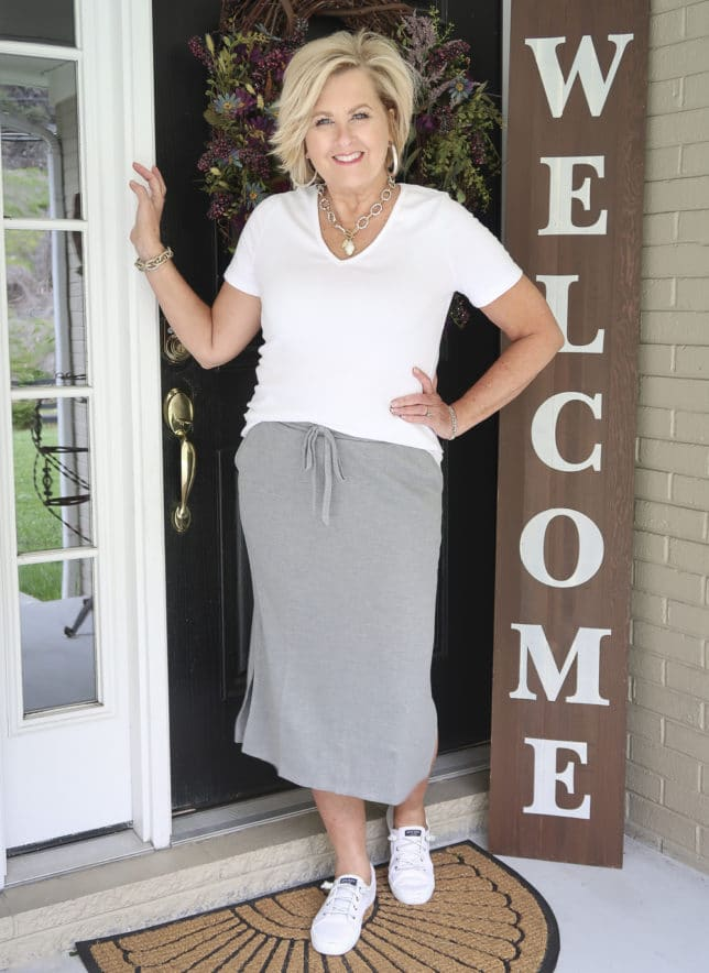 Fashion Blogger 50 Is Not Old is wearing a white v-neck t-shirt with a medium gray jogger pencil skirt, sneakers, and silver jewelry