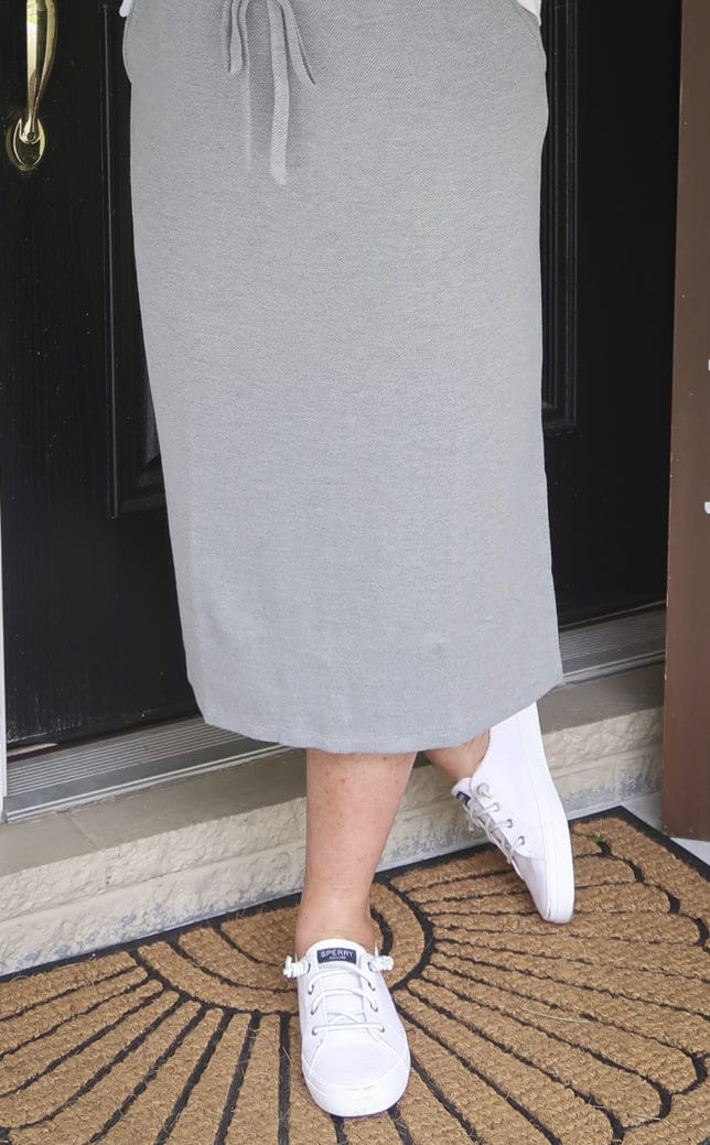 Fashion Blogger 50 Is Not Old is wearing a medium gray jogger pencil skirt and white Sperry sneakers