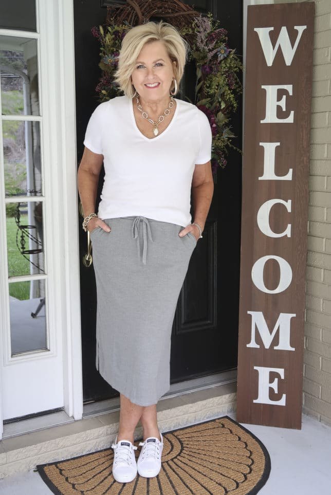 Fashion Blogger 50 Is Not Old is wearing a white t-shirt with a medium gray jogger pencil skirt, sneakers, and silver jewelry