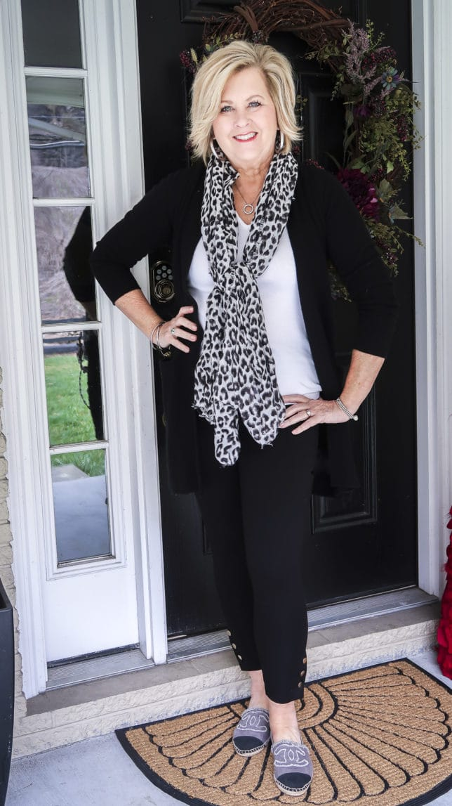 Fashion Blogger 50 Is Not Old is wearing a white tee, a black cardigan, black leggings, and a snow leopard scarf