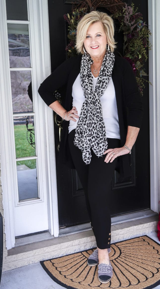 Fashion Blogger 50 Is Not Old is wearing a white t-shirt, a black cardigan, black leggings, and a snow leopard scarf
