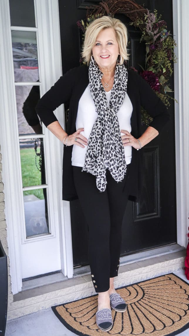Fashion Blogger 50 Is Not Old is wearing a white t-shirt, a long black cardigan, black leggings, and a snow leopard scarf
