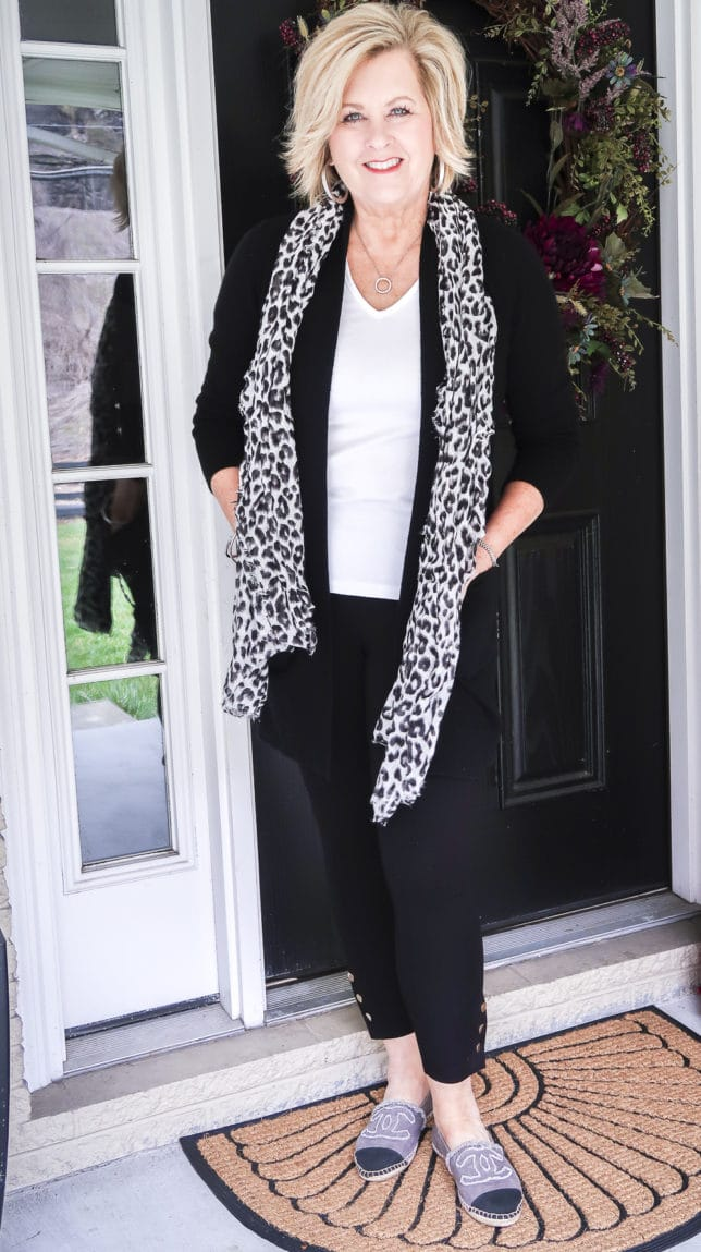 Fashion Blogger 50 Is Not Old is wearing a white t-shirt, a black cardigan, black leggings, and a black and white scarf