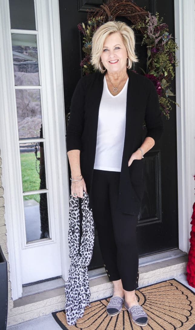 Fashion Blogger 50 Is Not Old is wearing a white t-shirt, a black cardigan, and black leggings