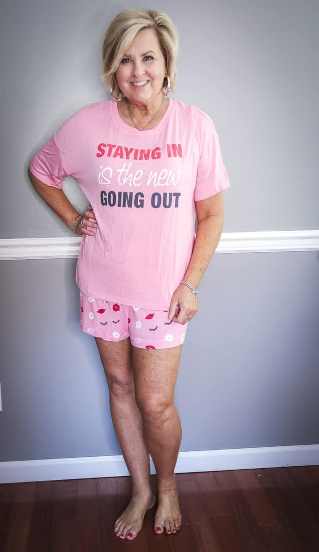 Fashion Blogger 50 Is Not Old wearing a short pink pajama set with lips and lashes