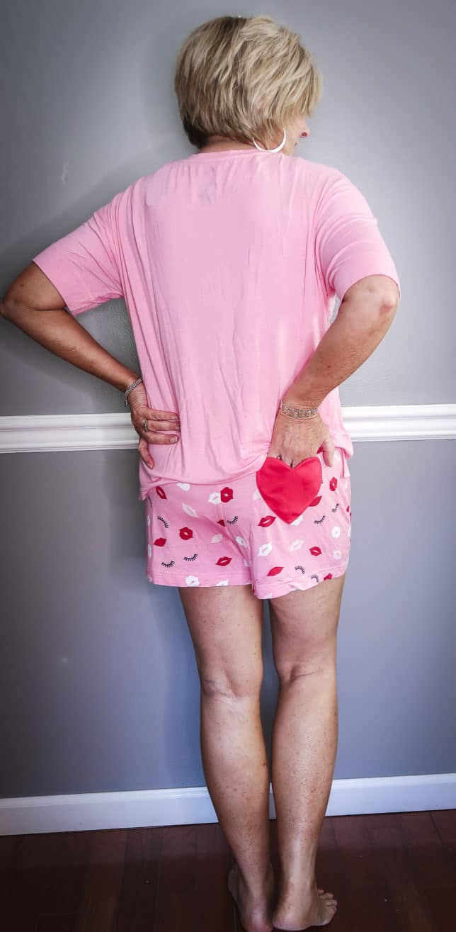 Fashion Blogger 50 Is Not Old wearing a short pink pajama set with a heart pocket on the butt