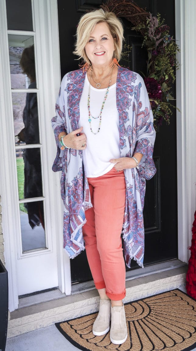 Fashion Blogger 50 Is Not Old wearing spring colors in a Ruana, and white t-shirt, and coral girlfriend jeans