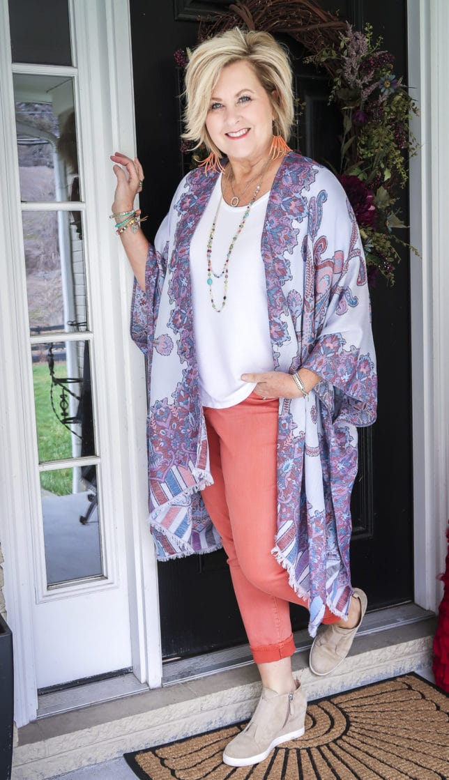 Fashion Blogger 50 Is Not Old wearing spring colors in a gorgeous Ruana, a white t-shirt, coral girlfriend jeans, and colorful jewelry