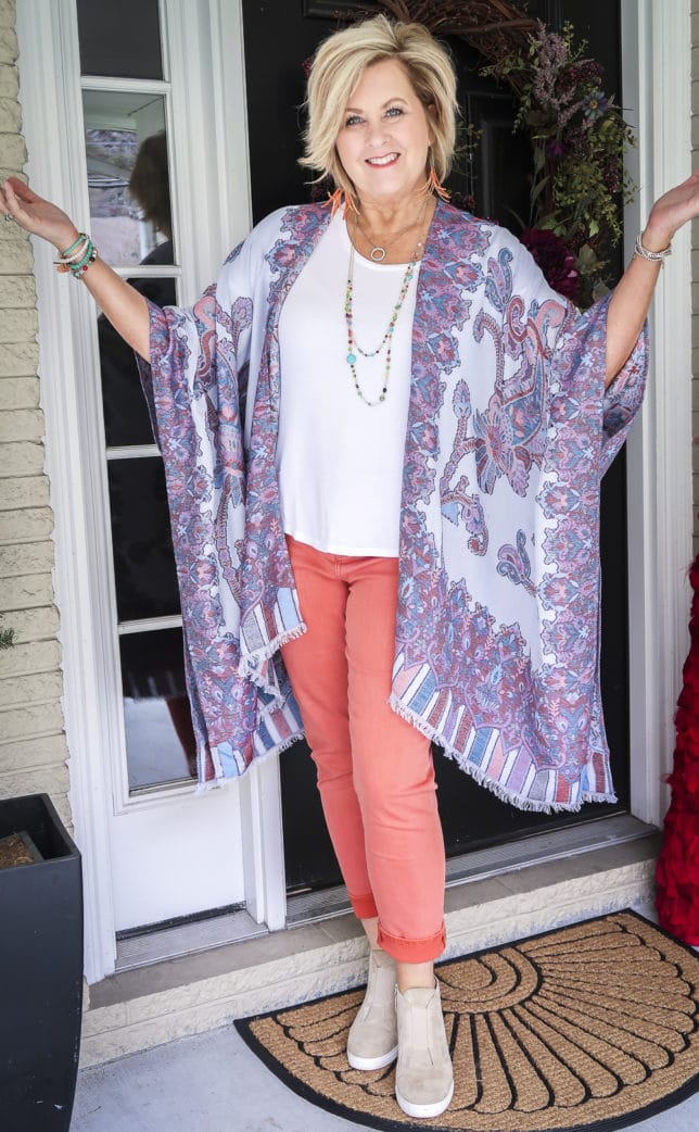 Fashion Blogger 50 Is Not Old wearing spring colors in a gorgeous Ruana, a white t-shirt, and coral girlfriend jeans