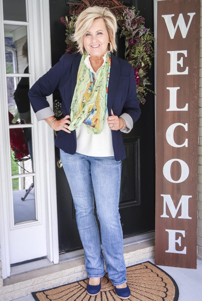 Fashion Blogger 50 Is Not Old is wearing a navy blazer with a colorful scarf, bootcut jeans, and navy shoes