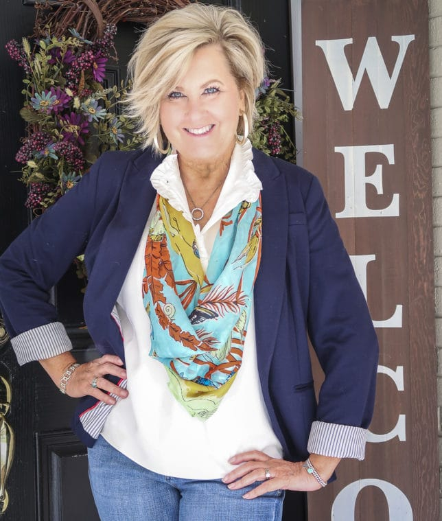 Fashion Blogger 50 Is Not Old wearing a navy blazer with a colorful scarf
