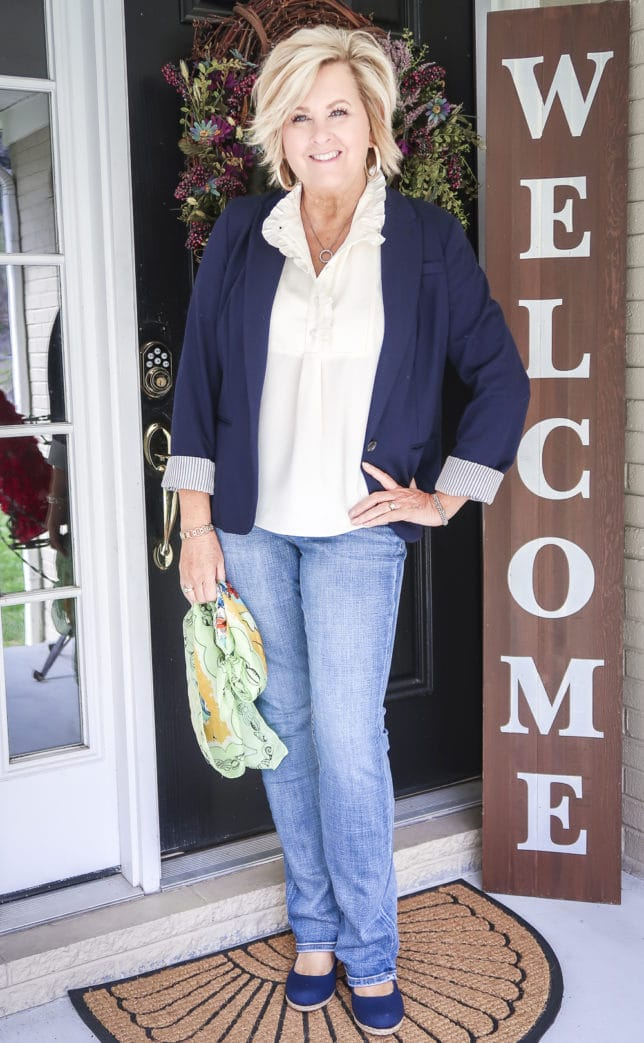 Fashion Blogger 50 Is Not Old is wearing a navy blazer, bootcut jeans, and navy espadrilles