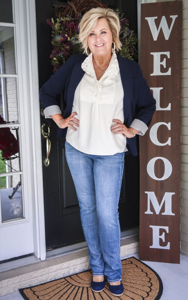Fashion Blogger 50 Is Not Old is wearing a navy blazer, a ruffled blouse, bootcut jeans, and navy espadrilles