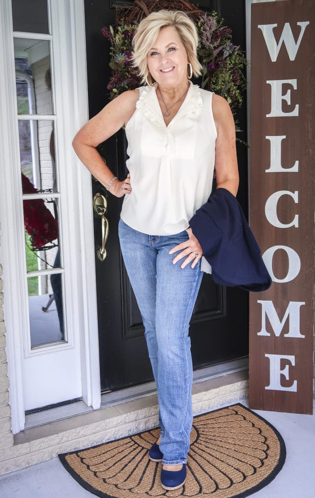 Fashion Blogger 50 Is Not Old is wearing a sleeveless blouse with ruffles, bootcut jeans, and navy espadrilles