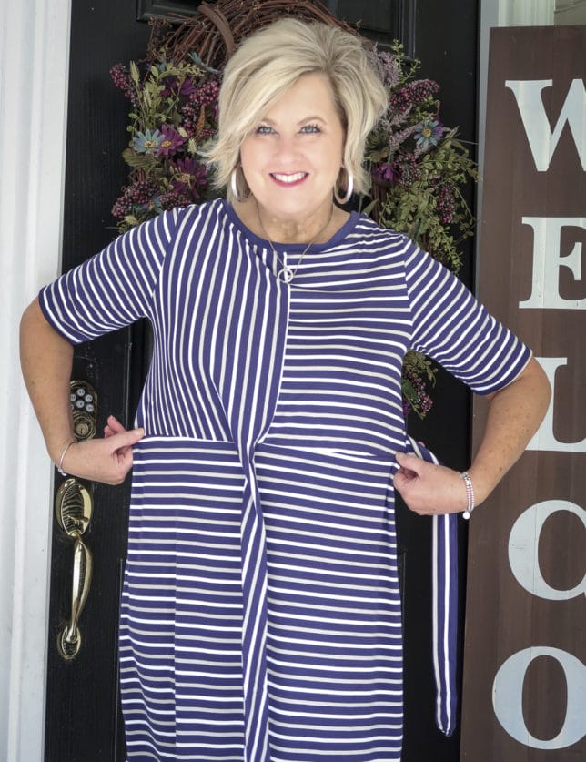 50 Is not Old is wearing a striped un-tied faux wrap dress