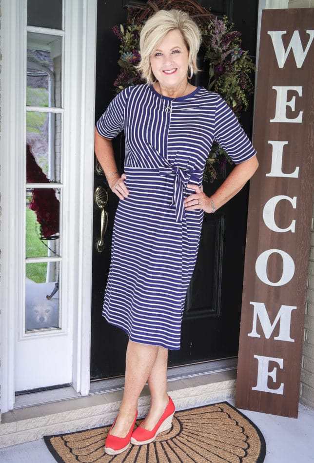 50 Is not Old is wearing a striped faux wrap dress with bright red espadrilles