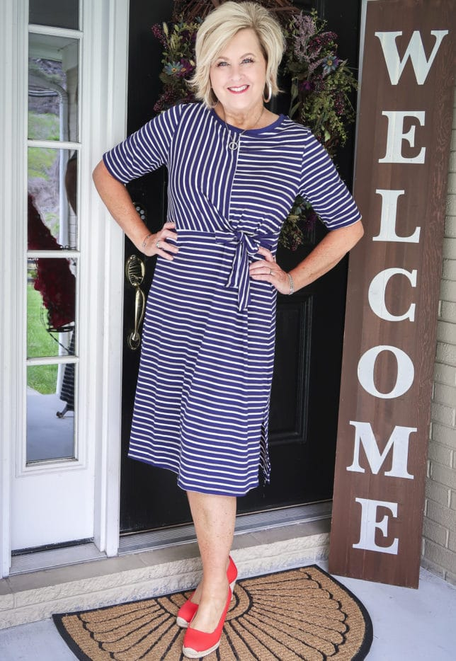 50 Is not Old is wearing a navy striped faux wrap dress with bright red espadrilles from J. Crew