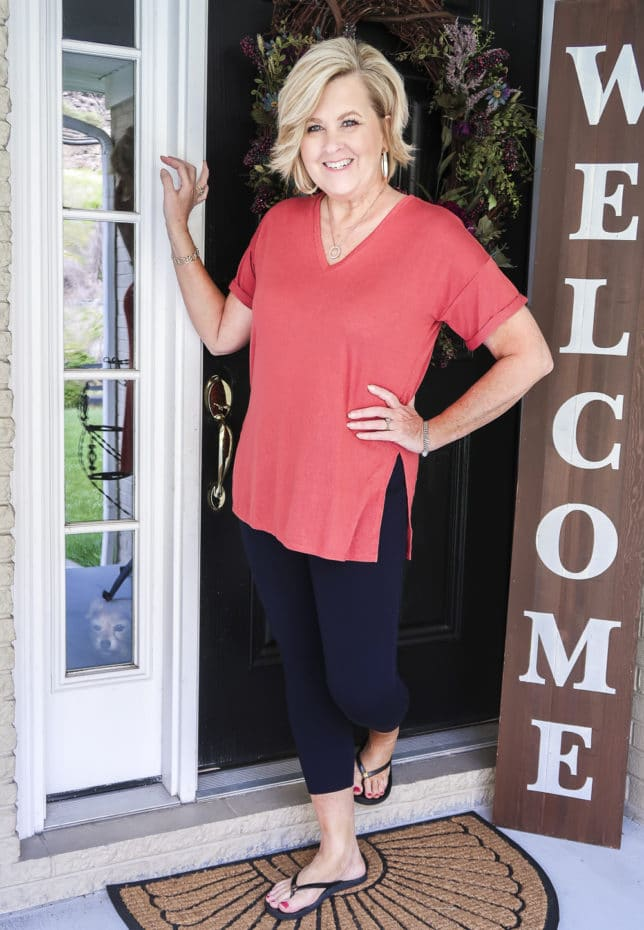 Fashion Blogger 50 Is Not Old is a relaxing rose colored v-neck tunic tee, navy Ponte knit leggings, and flip flops by Tory Burch.
