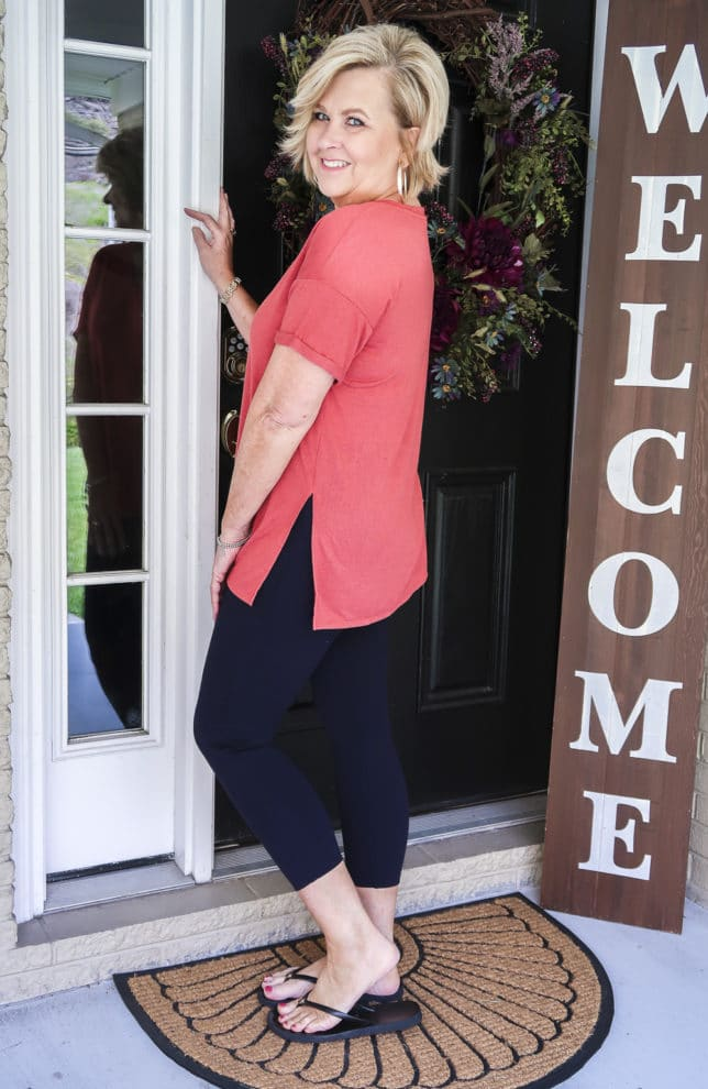 Fashion Blogger 50 Is Not Old is a relaxing rose colored v-neck tunic tee, navy Ponte leggings, and black flip flops by Tory Burch.