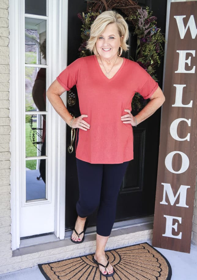 Fashion Blogger 50 Is Not Old is a relaxing rose v-neck tunic tee, navy Ponte knit leggings, and black flip flops by Tory Burch.