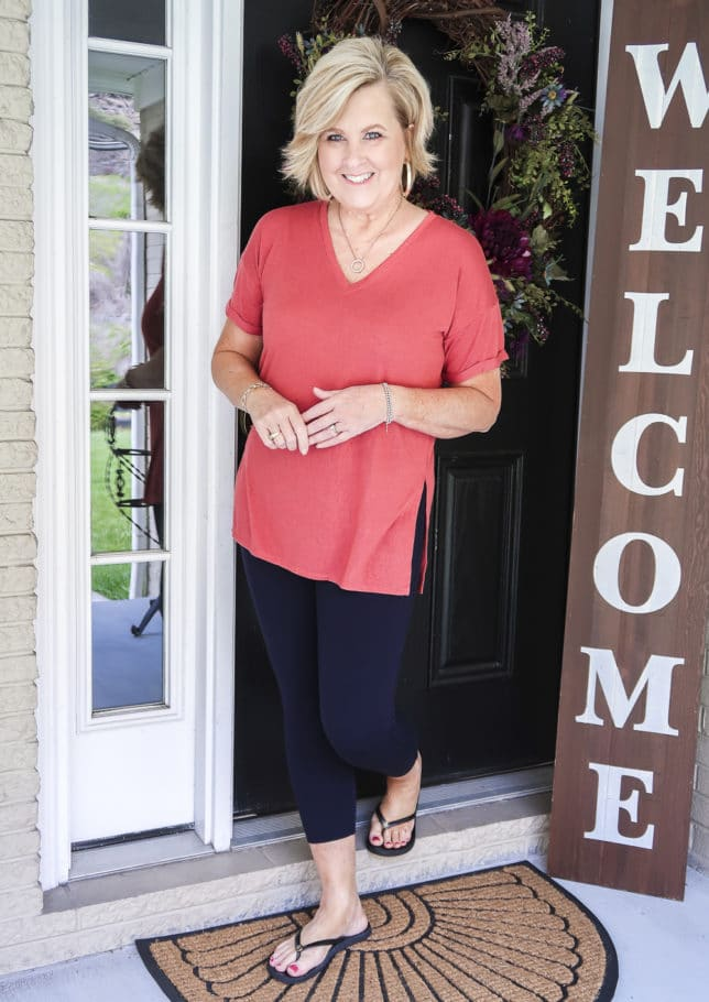 Fashion Blogger 50 Is Not Old is a relaxing rose colored v-neck tunic tee, Ponte knit leggings, and black flip flops by Tory Burch.
