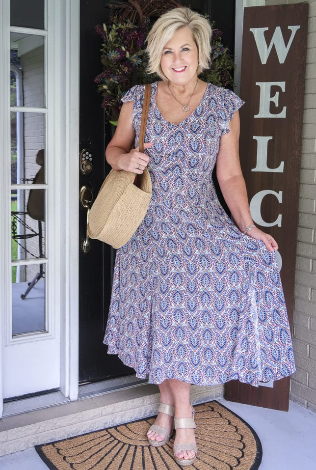 Fashion Blogger 50 Is Not Old wearing a gorgeous v-neck printed dress from Scoop, and round straw bag, and metallic gold espadrille sandals all available at Walmart
