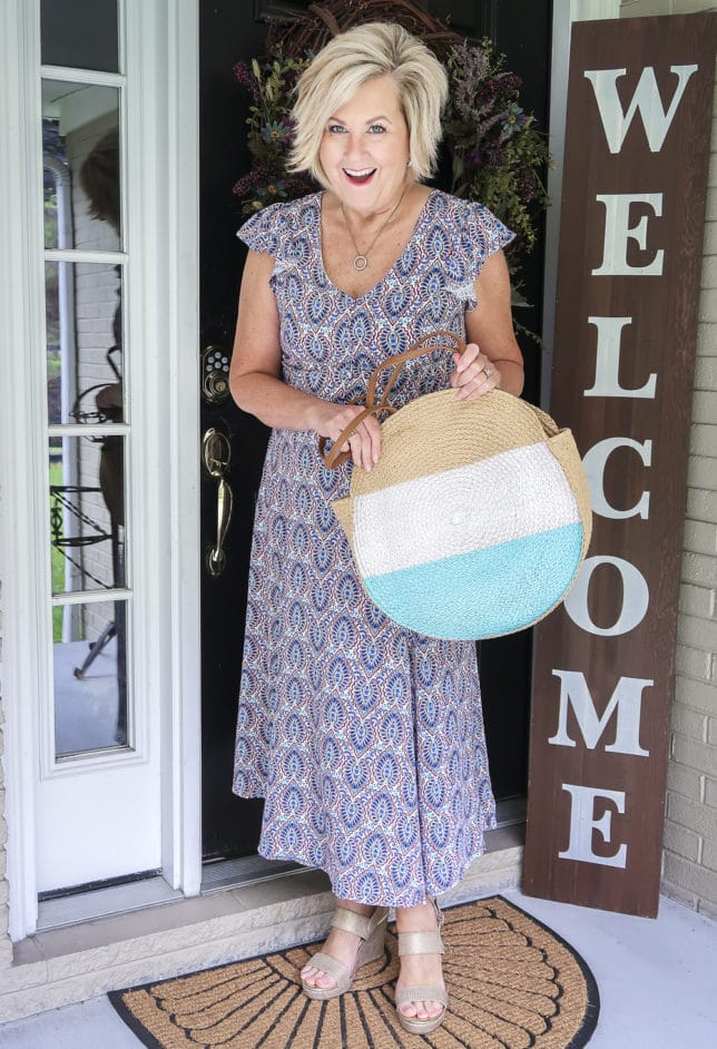Fashion Blogger 50 Is Not Old wearing a gorgeous v-neck printed dress from Scoop, and striped round straw bag, and metallic gold espadrille sandals all available at Walmart
