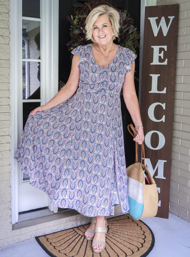 Fashion Blogger 50 Is Not Old wearing a gorgeous printed dress from Scoop, and round straw bag, and gold espadrille sandals all available at Walmart