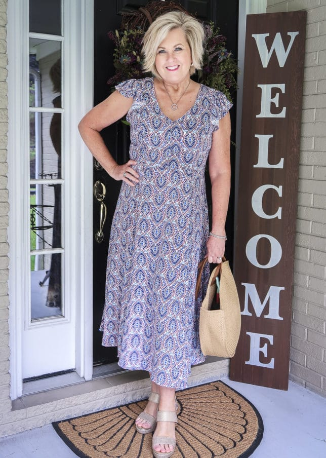 Fashion Blogger 50 Is Not Old wearing a gorgeous v-neck printed dress from Scoop, and round straw bag, and gold espadrille sandals all available at Walmart