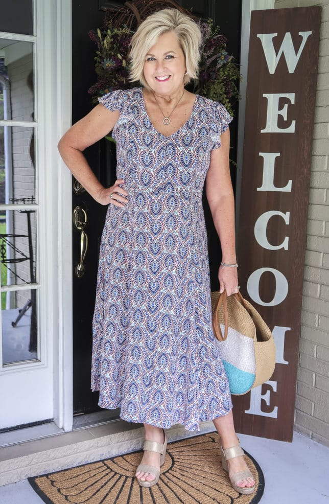 Fashion Blogger 50 Is Not Old wearing a gorgeous v-neck printed dress with flutter sleeves from Scoop, and round straw bag, and metallic gold espadrille sandals all available at Walmart