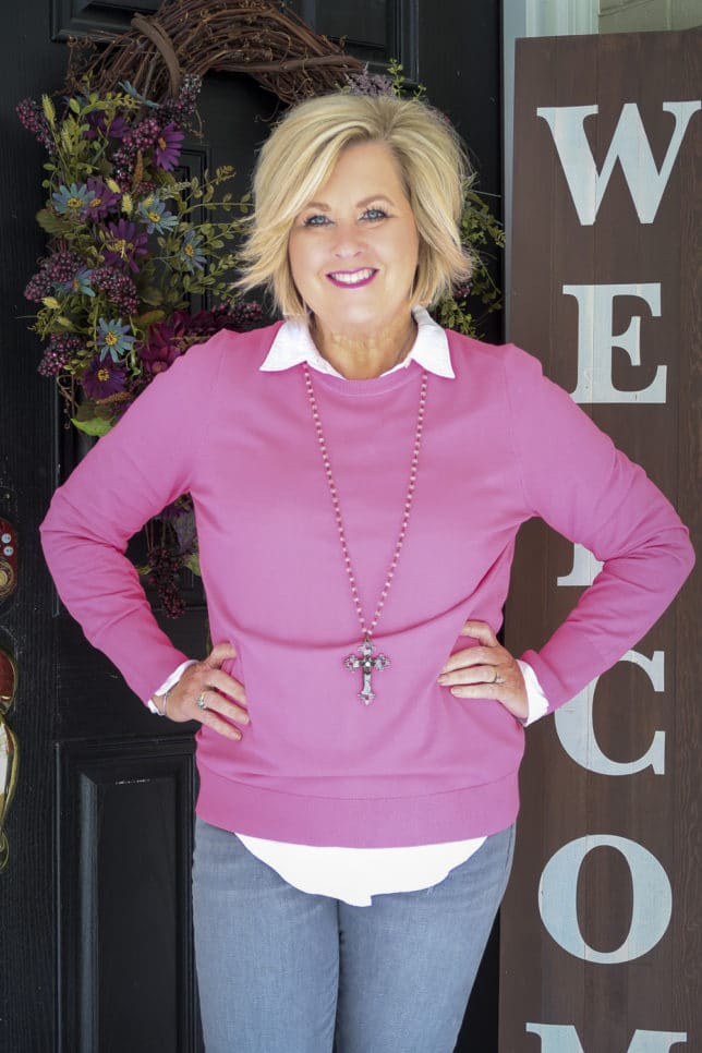 Fashion Blogger 50 Is Not Old wearing a while button down shirt and a pink sweater