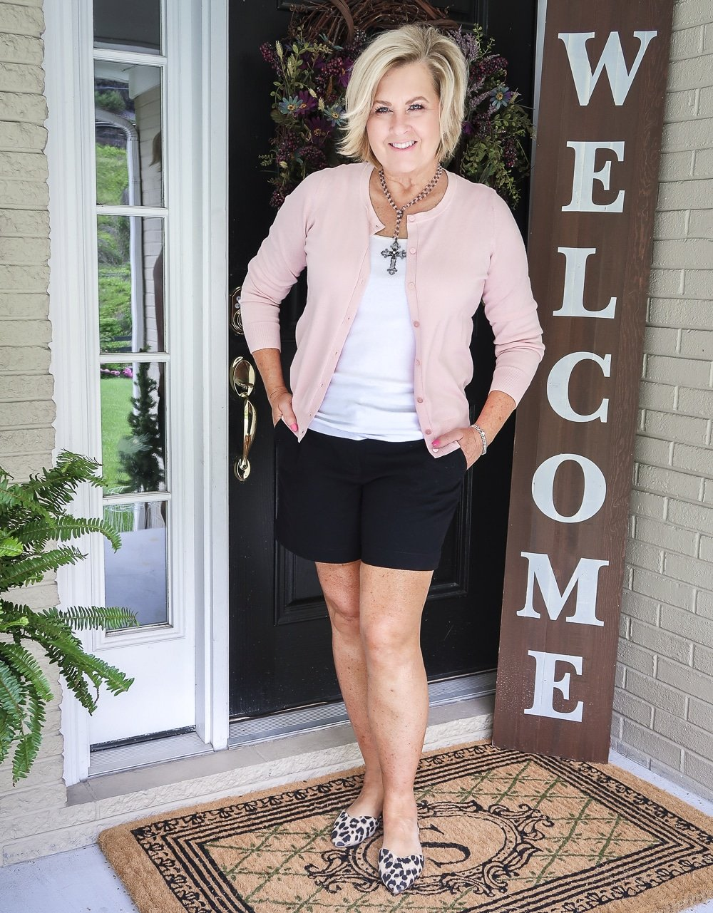 "Fashion Blogger 50 Is Not Old is wearing a soft pastel pink cardigan from Walmart, a white tank top, black 7"" shorts from Loft, and leopard print flats"