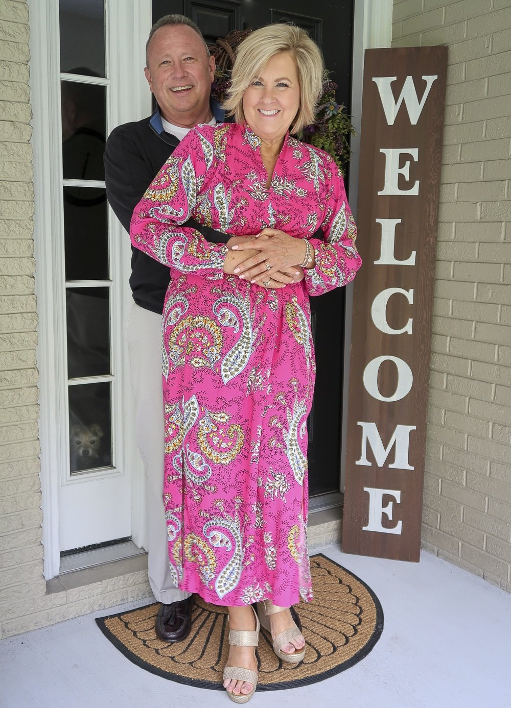 Fashion Blogger 50 Is Not Old and her husband are hugged up for a photo. She is wearing a bright pink paisley midi dress and gold espadrille sandals
