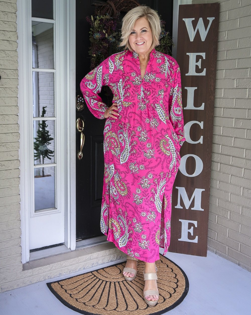 Fashion Blogger 50 Is Not Old is wearing a bright pink paisley midi dress and gold espadrille sandals