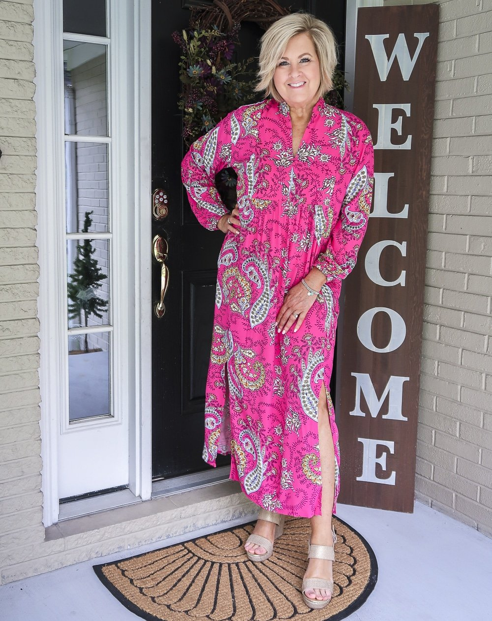 Fashion Blogger 50 Is Not Old is wearing a bright pink paisley midi dress with a side slit and gold espadrille sandals