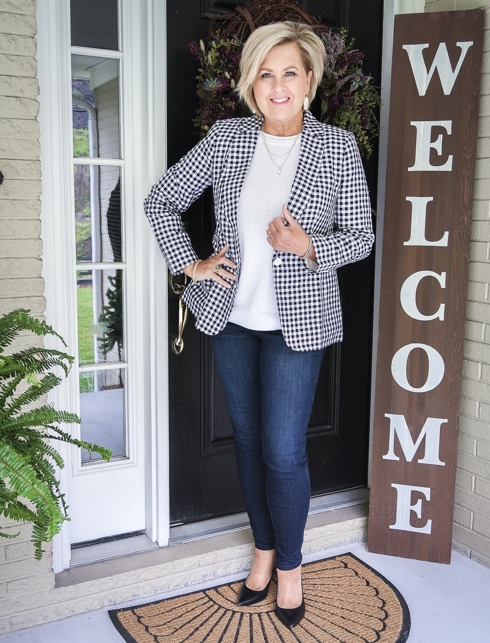 Fashion Blogger 50 Is Not Old is wearing a white sweater and a black and white gingham blazer with skinny jeans and black pumps