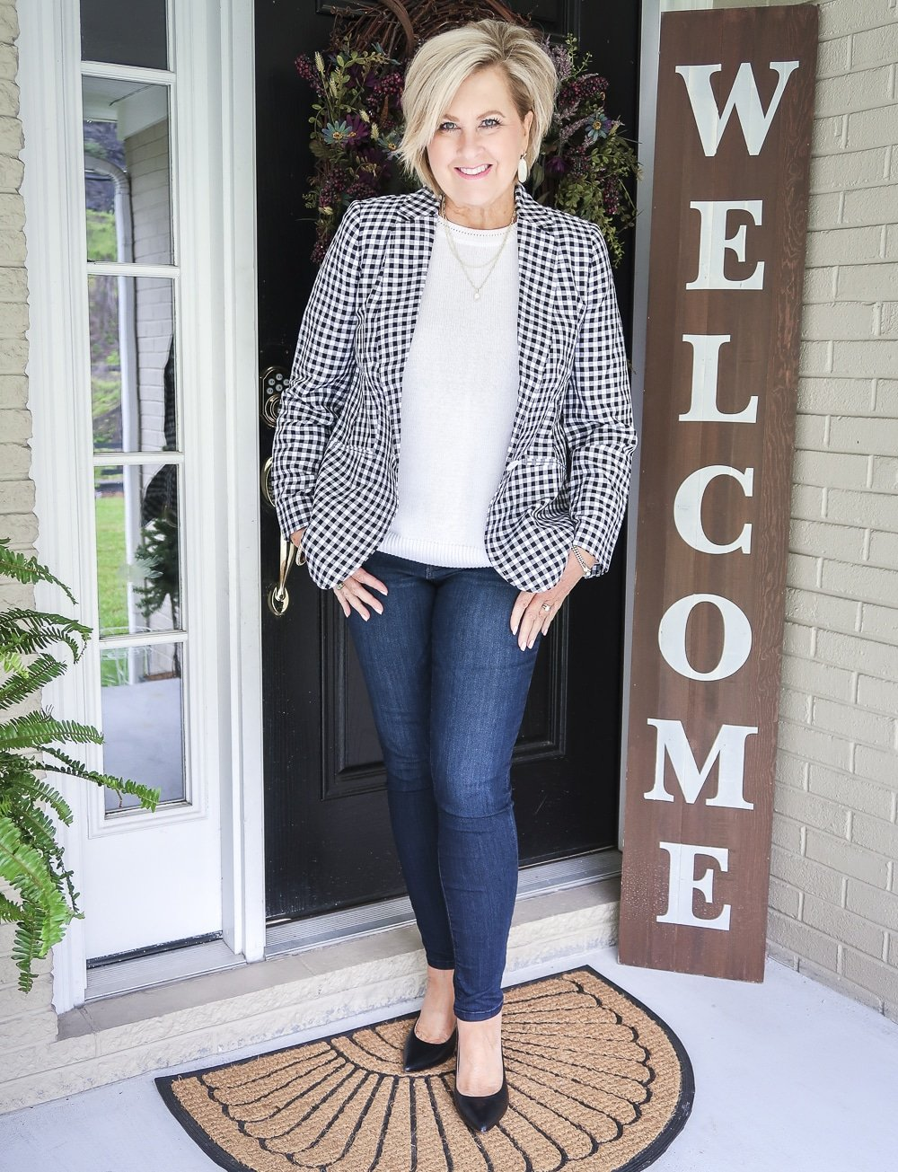 Fashion Blogger 50 Is Not Old is wearing a white sweater and a black and white gingham blazer with dark wash skinny jeans