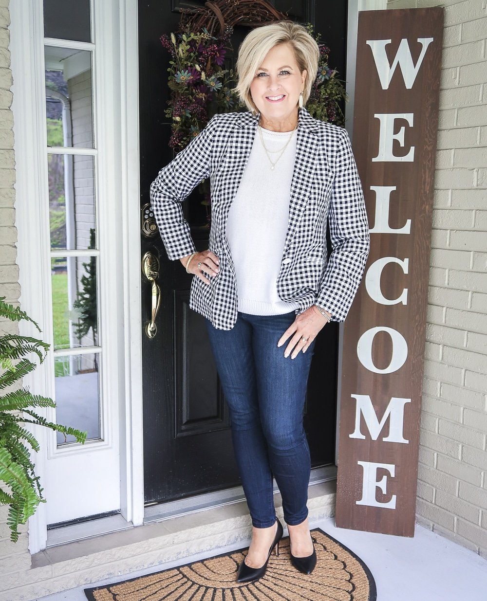 Fashion Blogger 50 Is Not Old is wearing a white sweater and a black and white gingham blazer with dark skinny jeans and black pumps