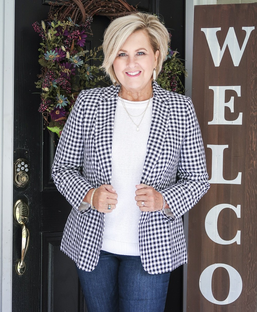 Fashion Blogger 50 Is Not Old is wearing a white sweater and a gingham blazer