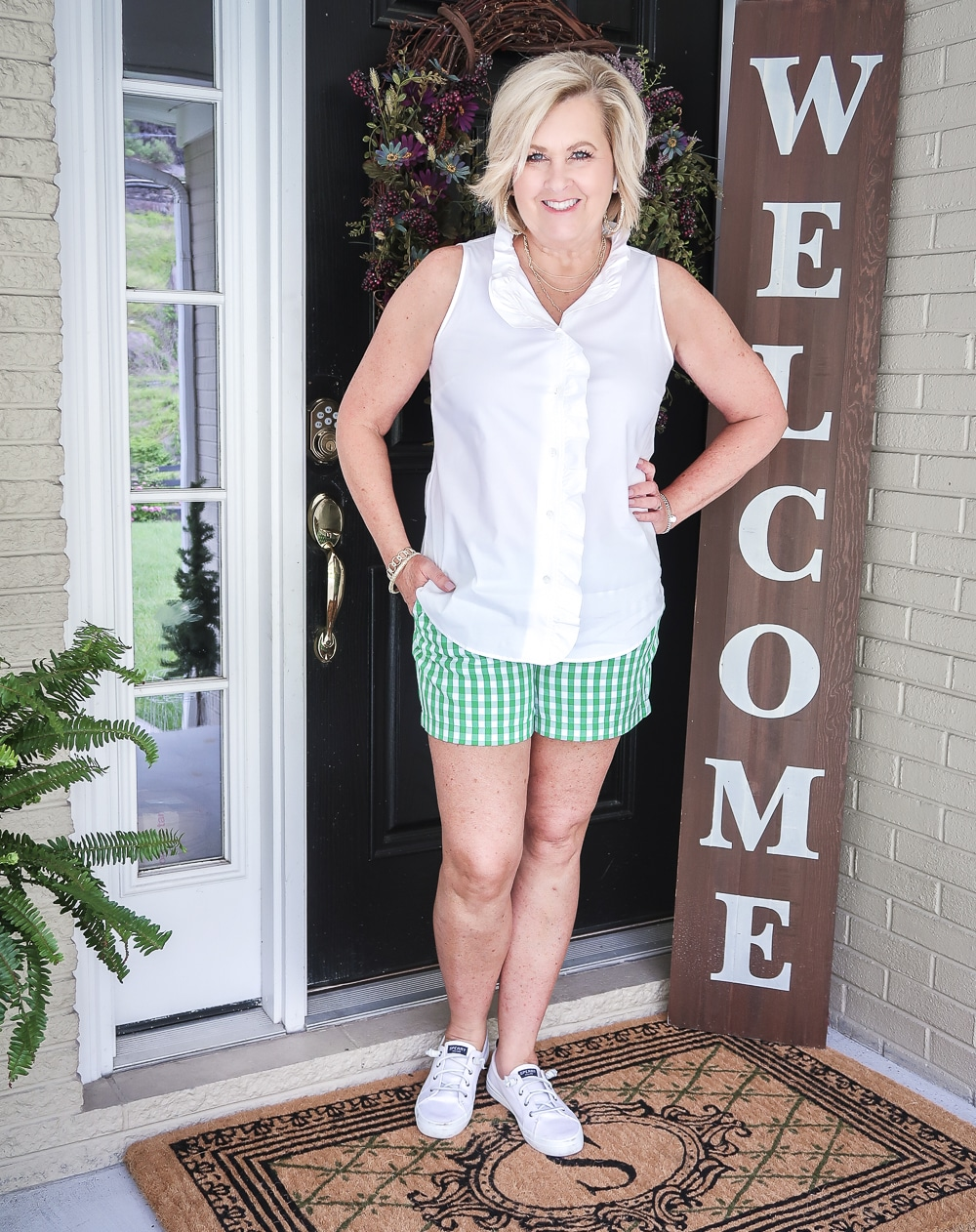FASHION BLOGGER 50 Is Not Old wearing a sleeveless top with a ruffled placket and green gingham shorts with a pair of Sperry slip on sneakers.