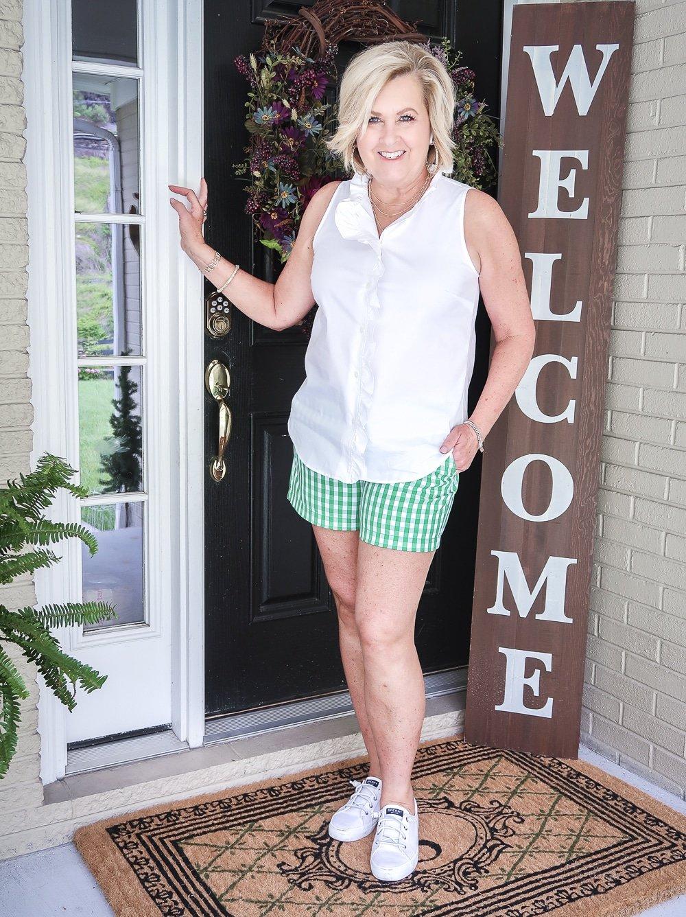 FASHION BLOGGER 50 Is Not Old wearing a sleeveless top with a ruffled placket and green gingham shorts with a pair of slip on sneakers.