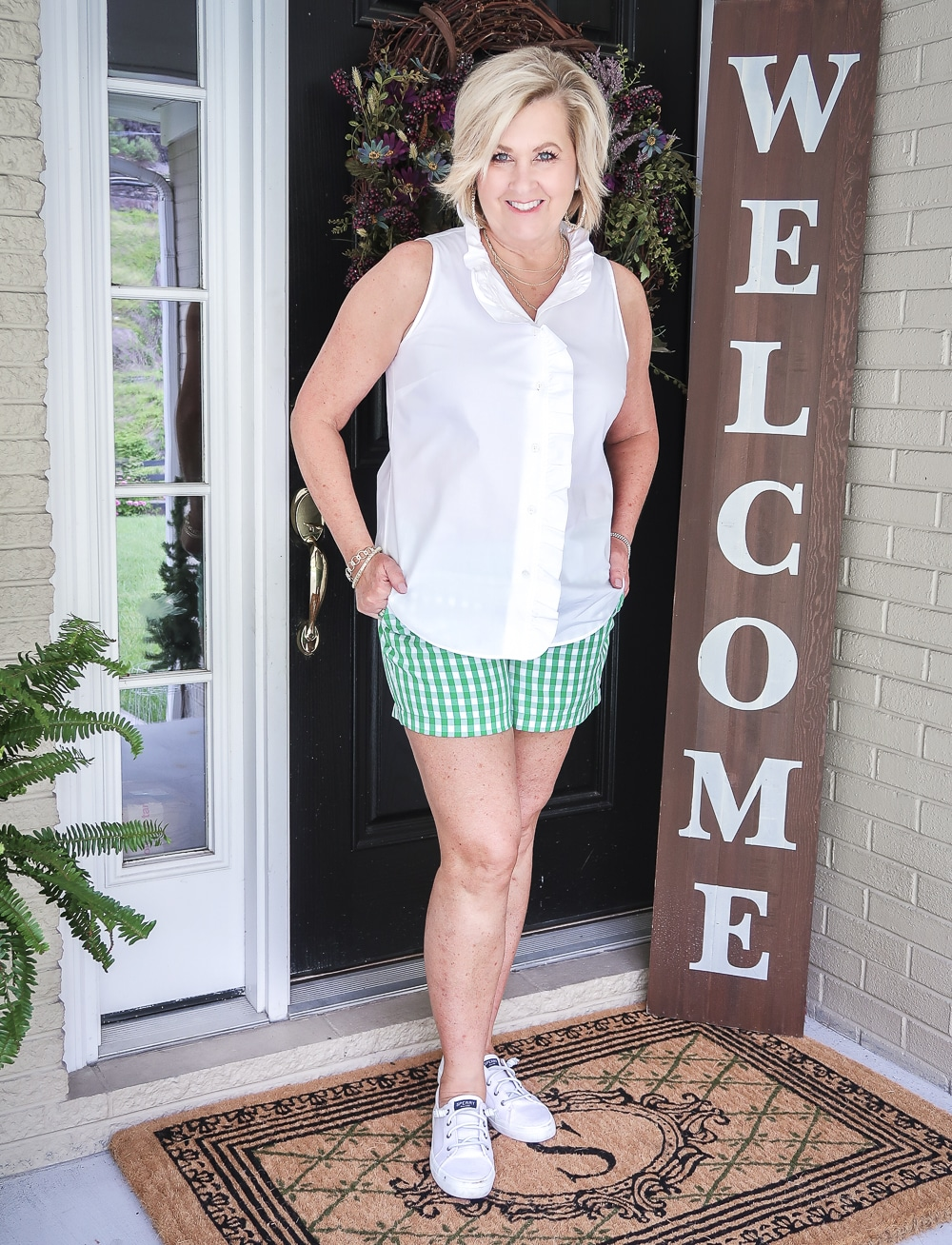 FASHION BLOGGER 50 Is Not Old wearing a sleeveless top with a ruffled placket and green gingham shorts with a pair of white Sperry slip on sneakers.