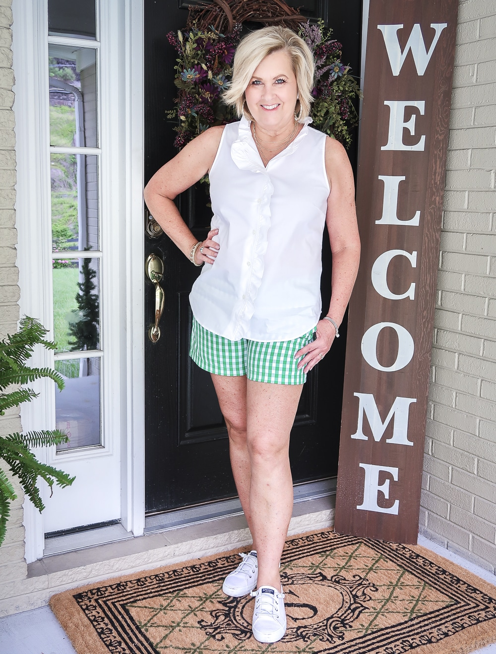 FASHION BLOGGER 50 Is Not Old wearing a sleeveless top with a ruffled neckline and green gingham shorts with a pair of Sperry slip on sneakers.
