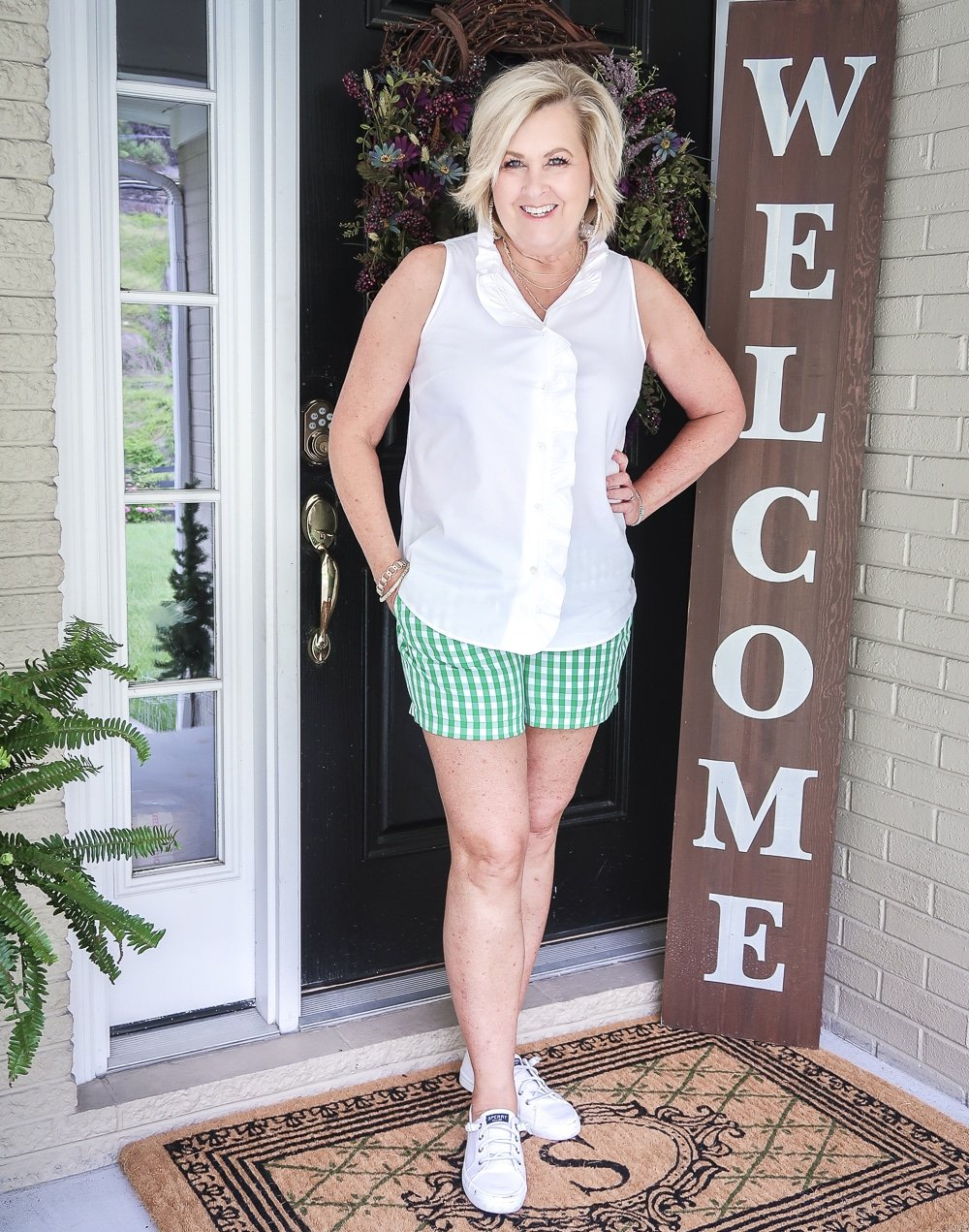 FASHION BLOGGER 50 Is Not Old wearing a sleeveless top with a ruffled placket and green gingham shorts with a pair of white slip on sneakers.