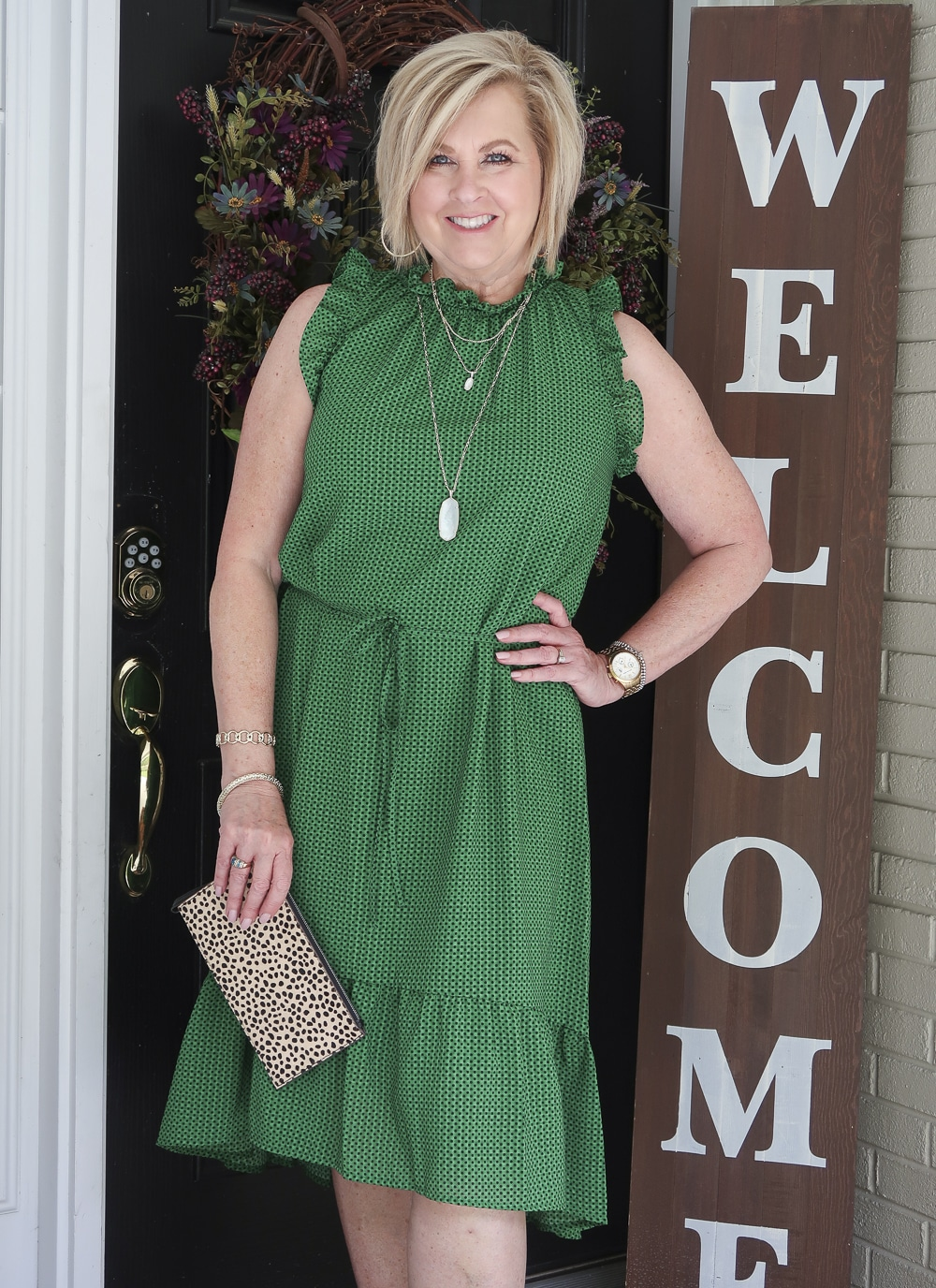 Fashion Blogger 50 Is Not Old is wearing a green polka dotted dress that has a high neck and ruffles plus gold jewelry from Kendra Scott