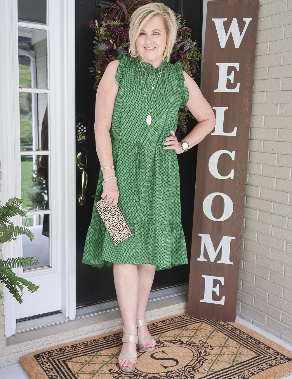 Fashion Blogger 50 Is Not Old is wearing a green polka dotted dress that has ruffles plus gold wedge shoes